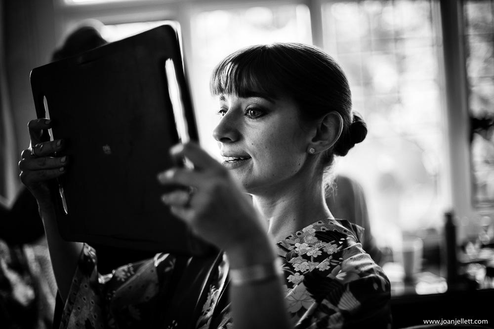 black and white shot of bridesmaid doing her mascara