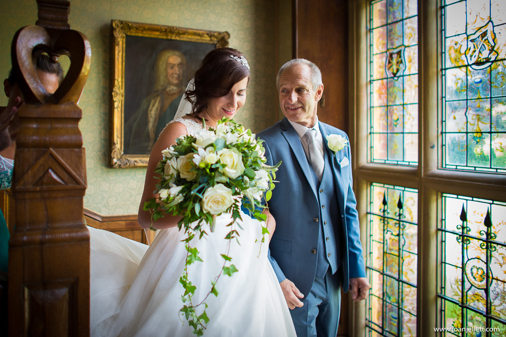 Bride and her father walking down the stairs at Hanbury manor