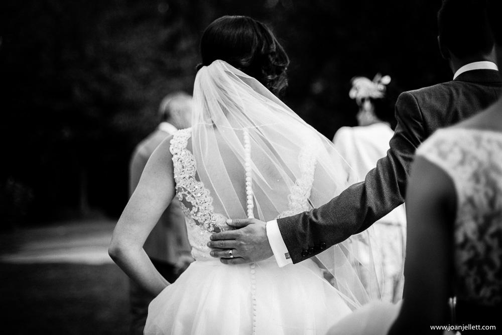 hand detail of groom hugging bride