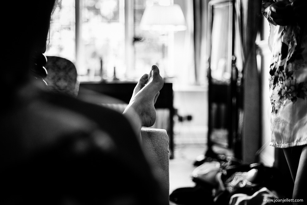 detail shot of feet up on sofa during bridal prep in black and white
