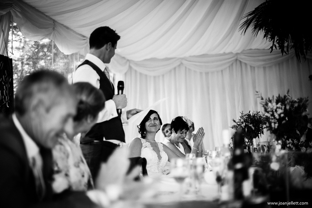 black and white shot of groom's speech and bride