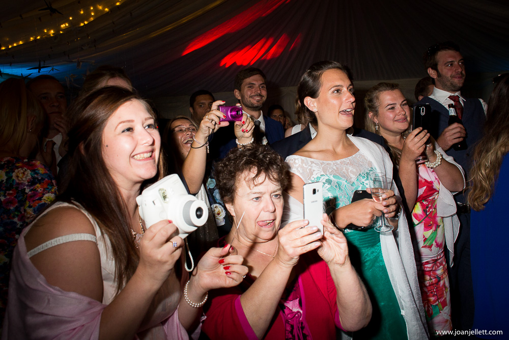 guests taking pictures of the first dance