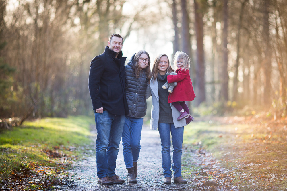 4 family members smiling in the woods