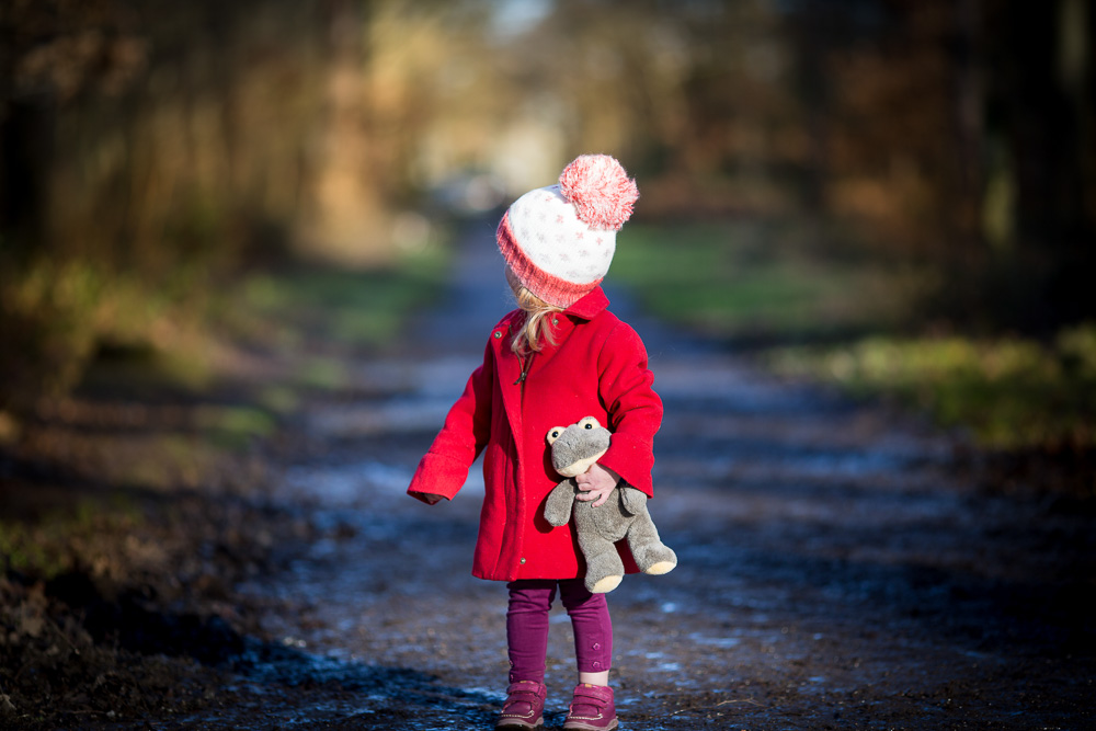 little girl in a red coat looking back