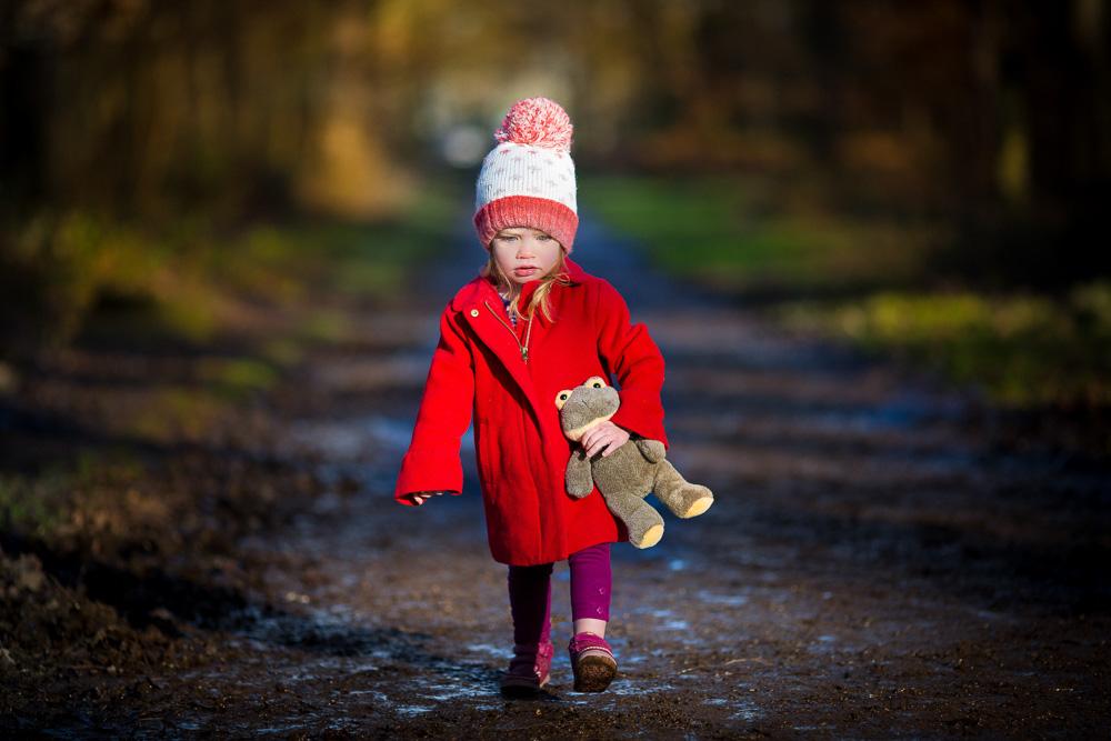 little girl in a red coat walking in the woods