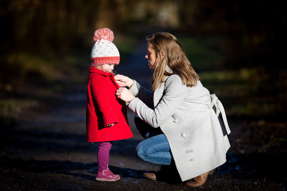 mother doing coat up of her daughter