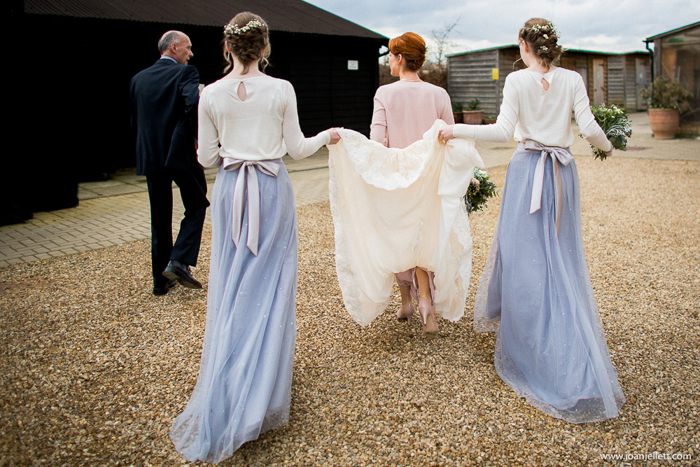 Bridesmaids holding up the bride's dress