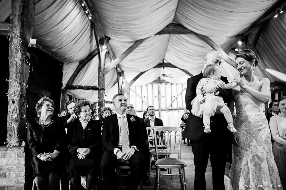 bride and groom hugging baby daughter