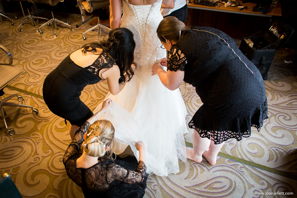 bride getting her dress on with bridesmaids