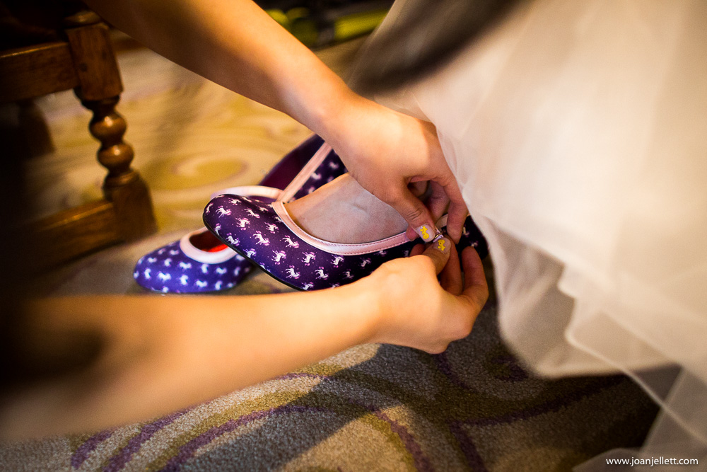 bride putting her unicorn shoes on