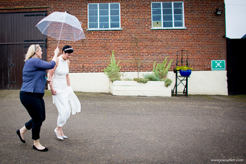 bride walking down to the venue under an umbrella