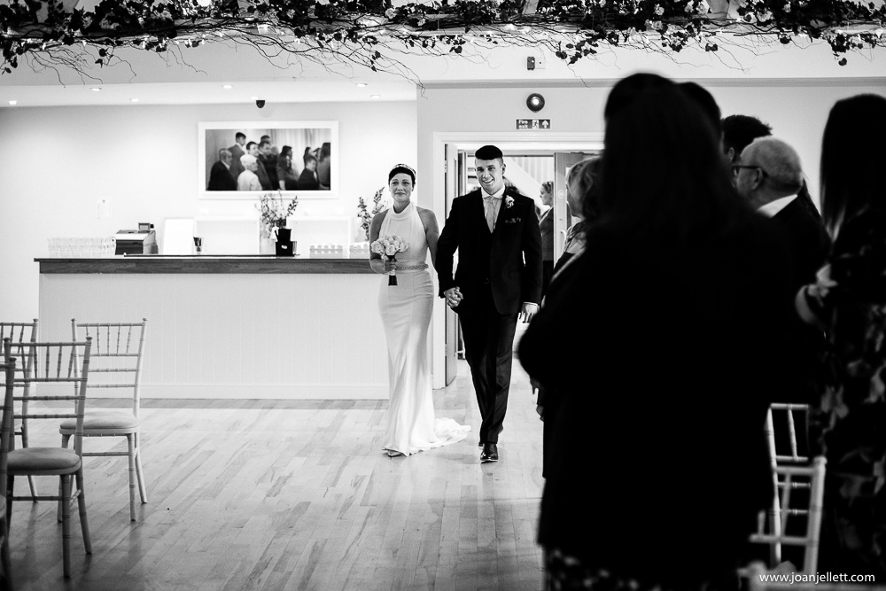 bride walking down the aisle in black and white