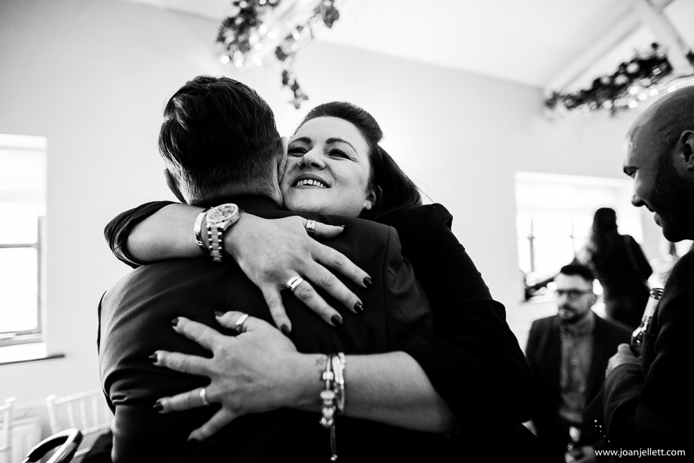 guests hugging and kissing in black and white