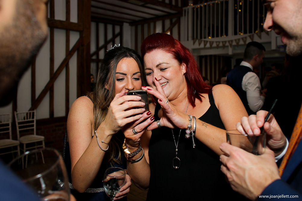 2 lady guests looking at a phone
