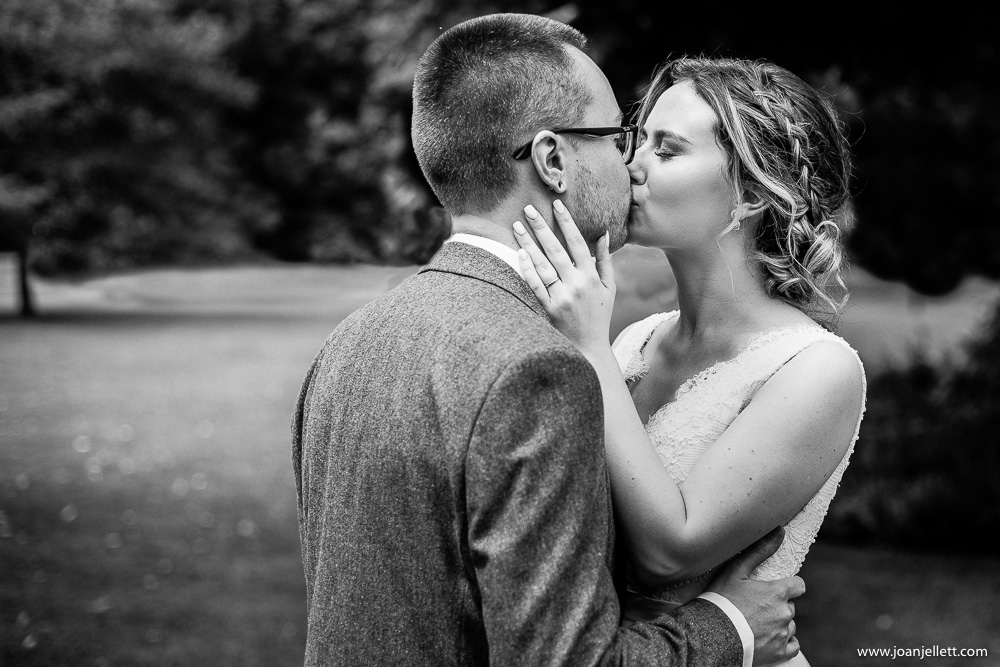black and white shot of bride kissing her groom