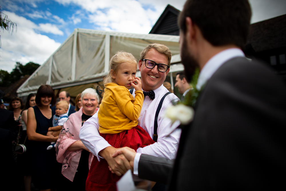 guests smiling holding a baby in his arms