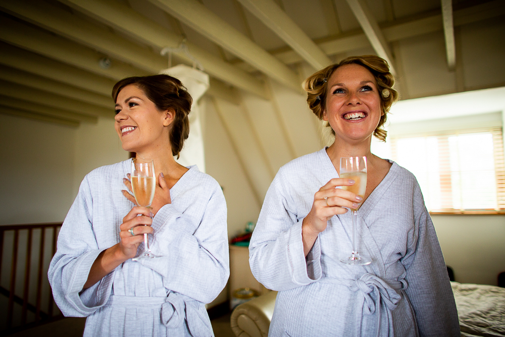 bridesmaids laughing with eachother drinking champagne