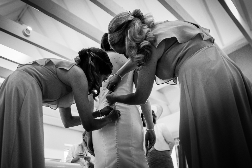 black and white shot of bridesmaids doing bride's dress up