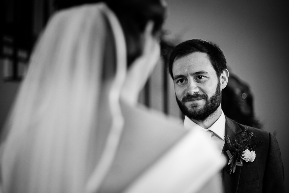 groom looking at his bride in black and white
