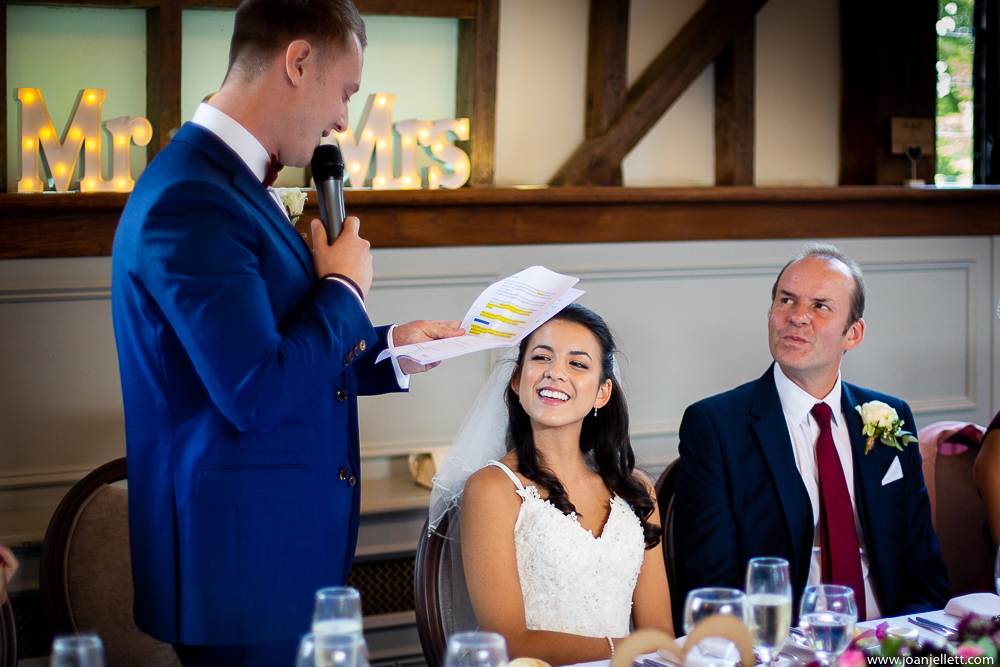 bride smiling at her groom's speech