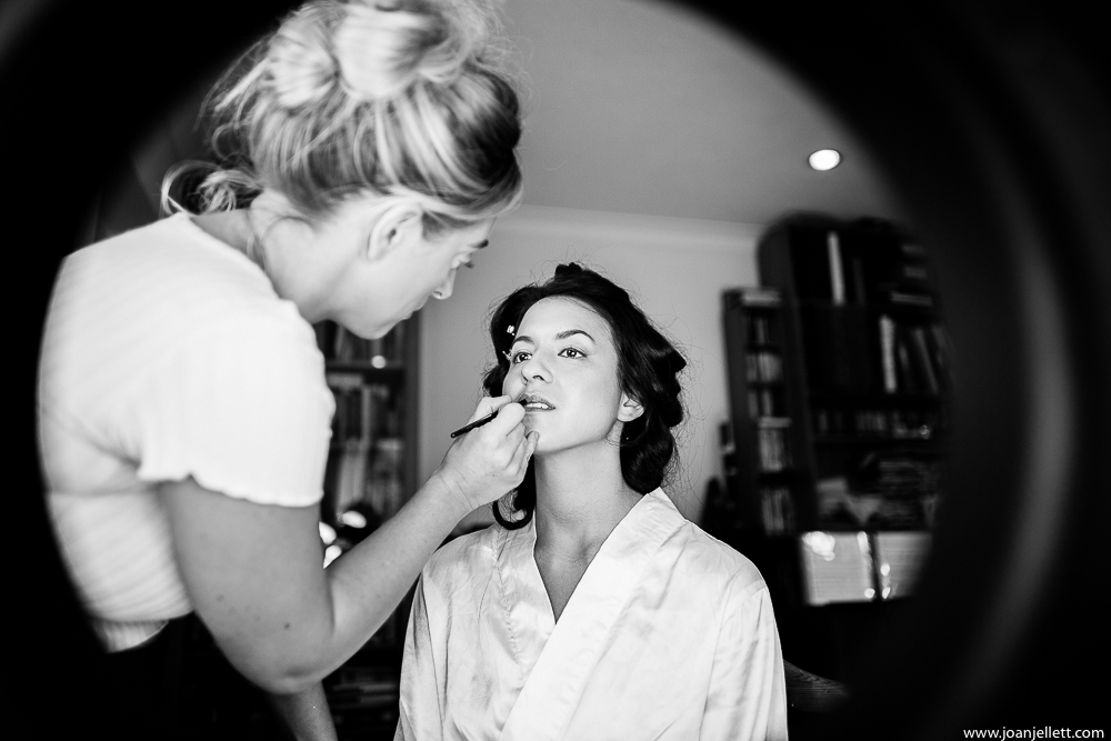 black and white shot of bride having makeup done