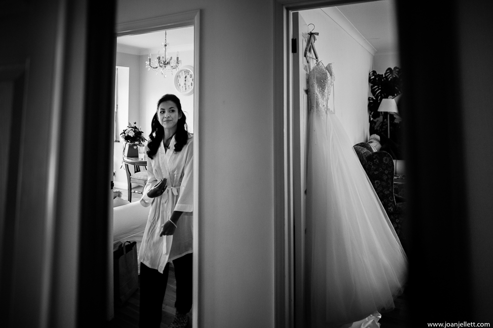 bride looking at her dress hanged