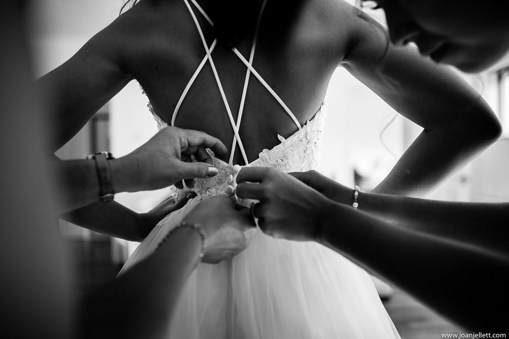 bride's dress being buttoned up