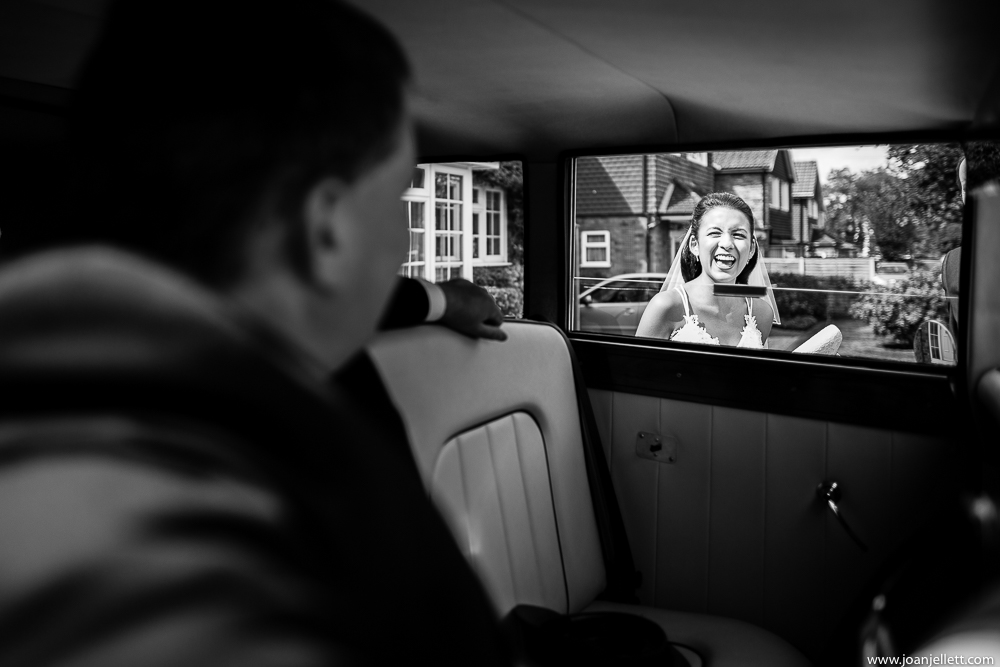 bride smiling as she gets in her car