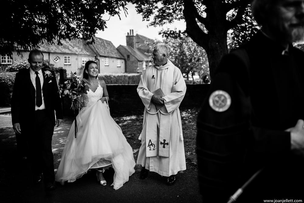bride smiling at priest
