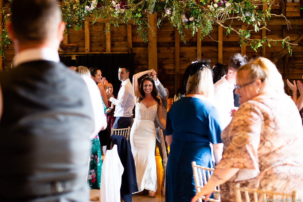 bride and groom entering the barn for their wedding breakfast