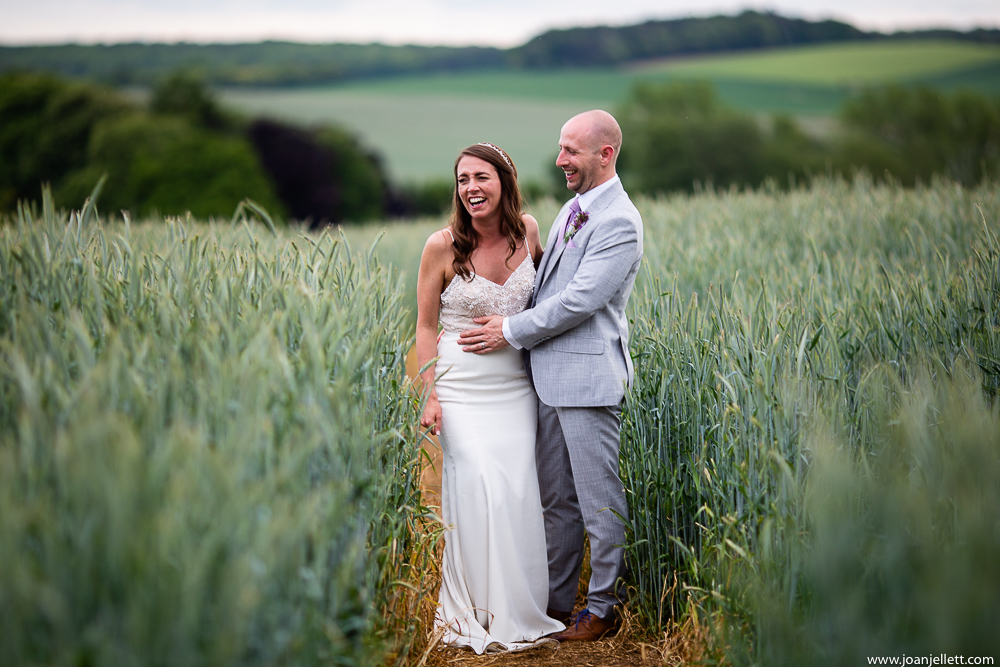 bride and groom in a field laughing