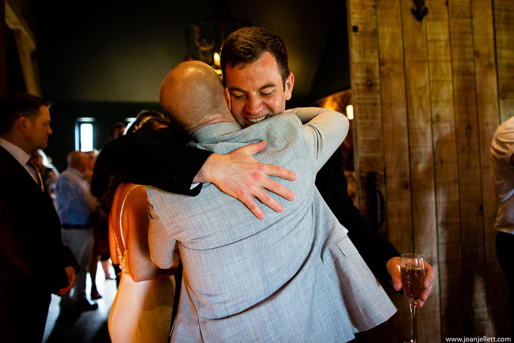 guests hugging the groom
