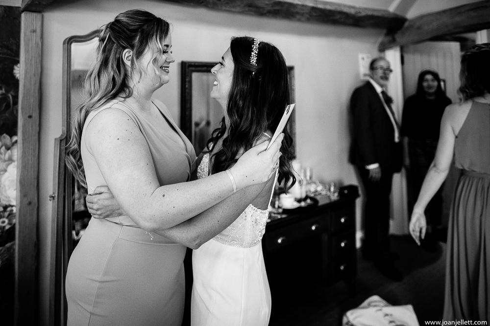 bridesmaid and bride hugging