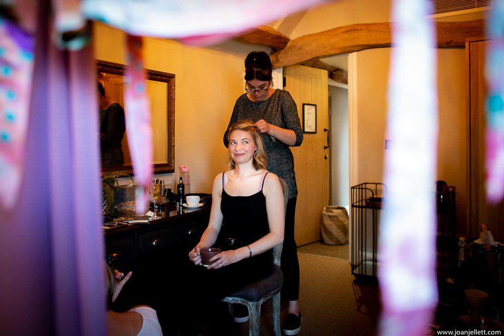 bridesmaid having her hair done at farmhouse at redcoats