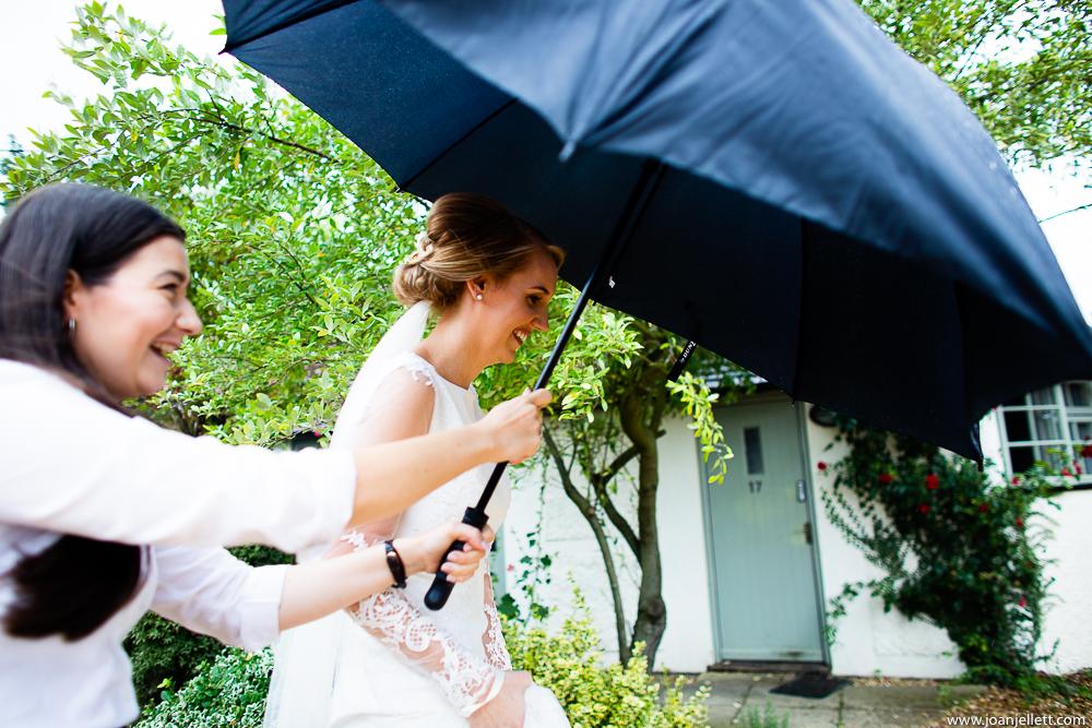bride walking under umbrella