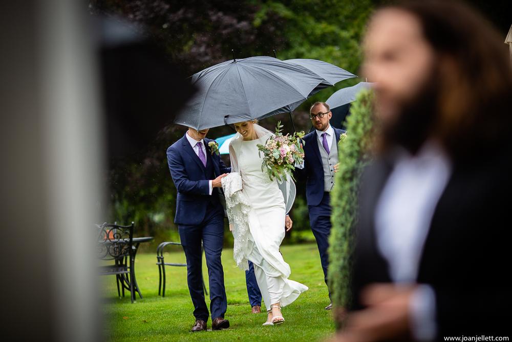 bride walking under umbrella for portraits