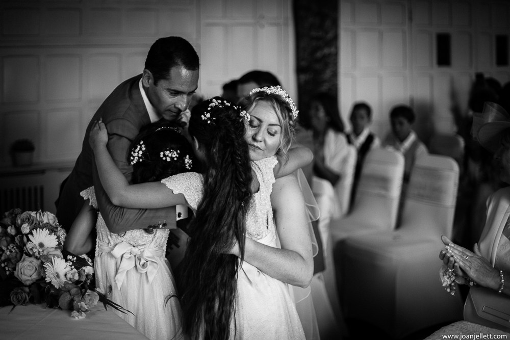 Bride and groom hugging their daughters