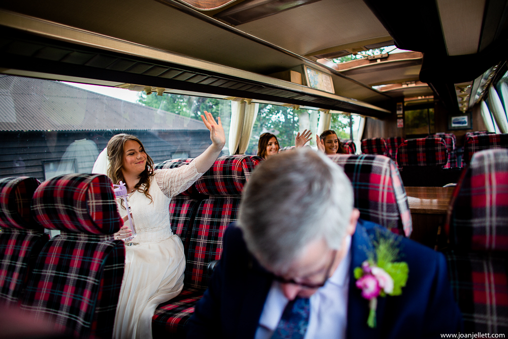 bride waving at her guests from the bus