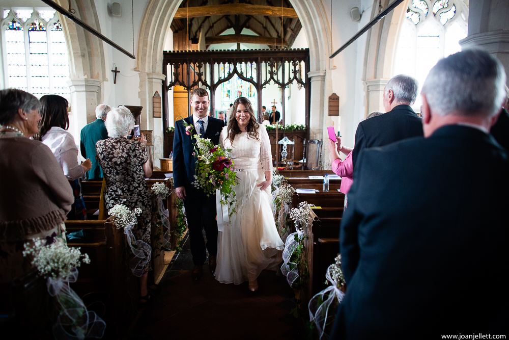just married walking down the church aisle