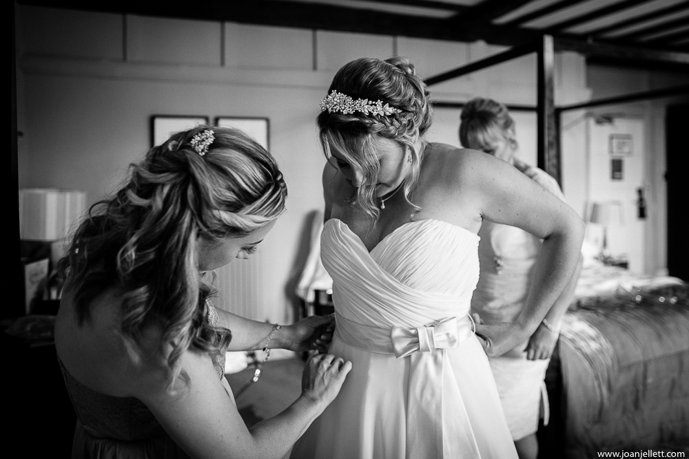 black and white shot of bride putting her dress on