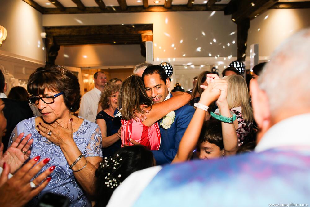 groom hugging his guest on the dance floor