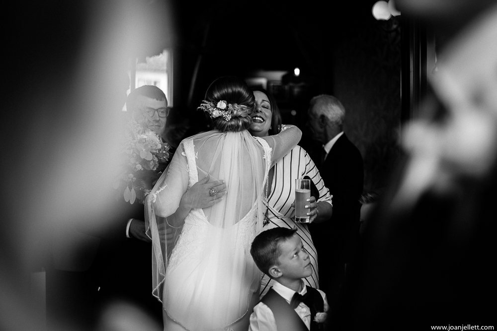 black and white shot of the bride greeting guests