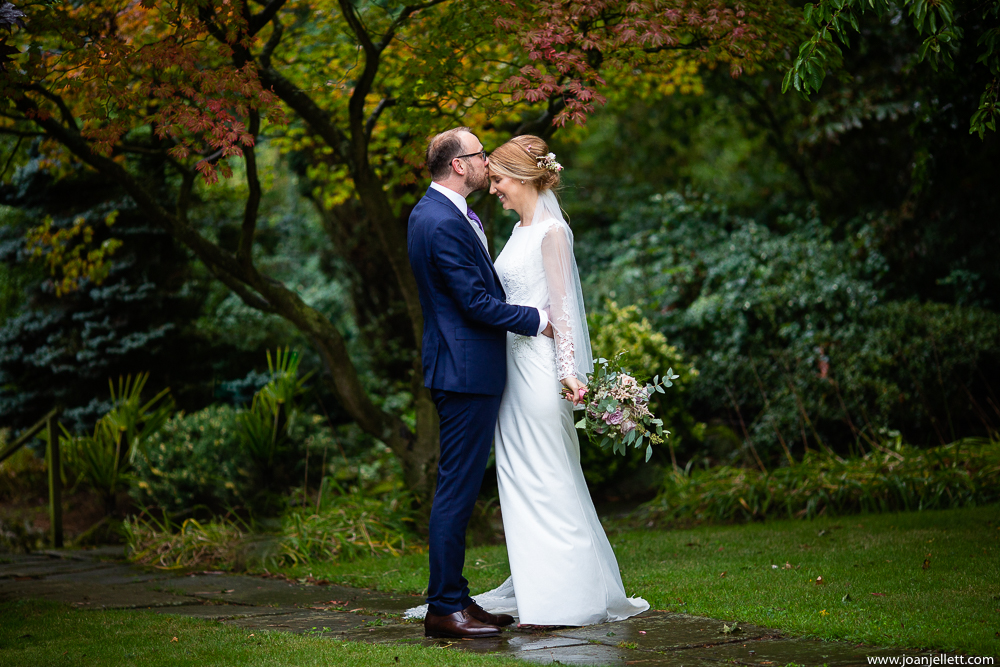 groom kissing his bride's head