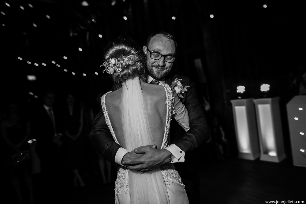 black and white shot of the bride and groom dancing