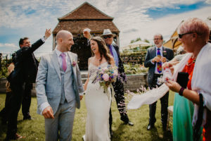 confetti shot of bride and groom looking at each other whilst walking