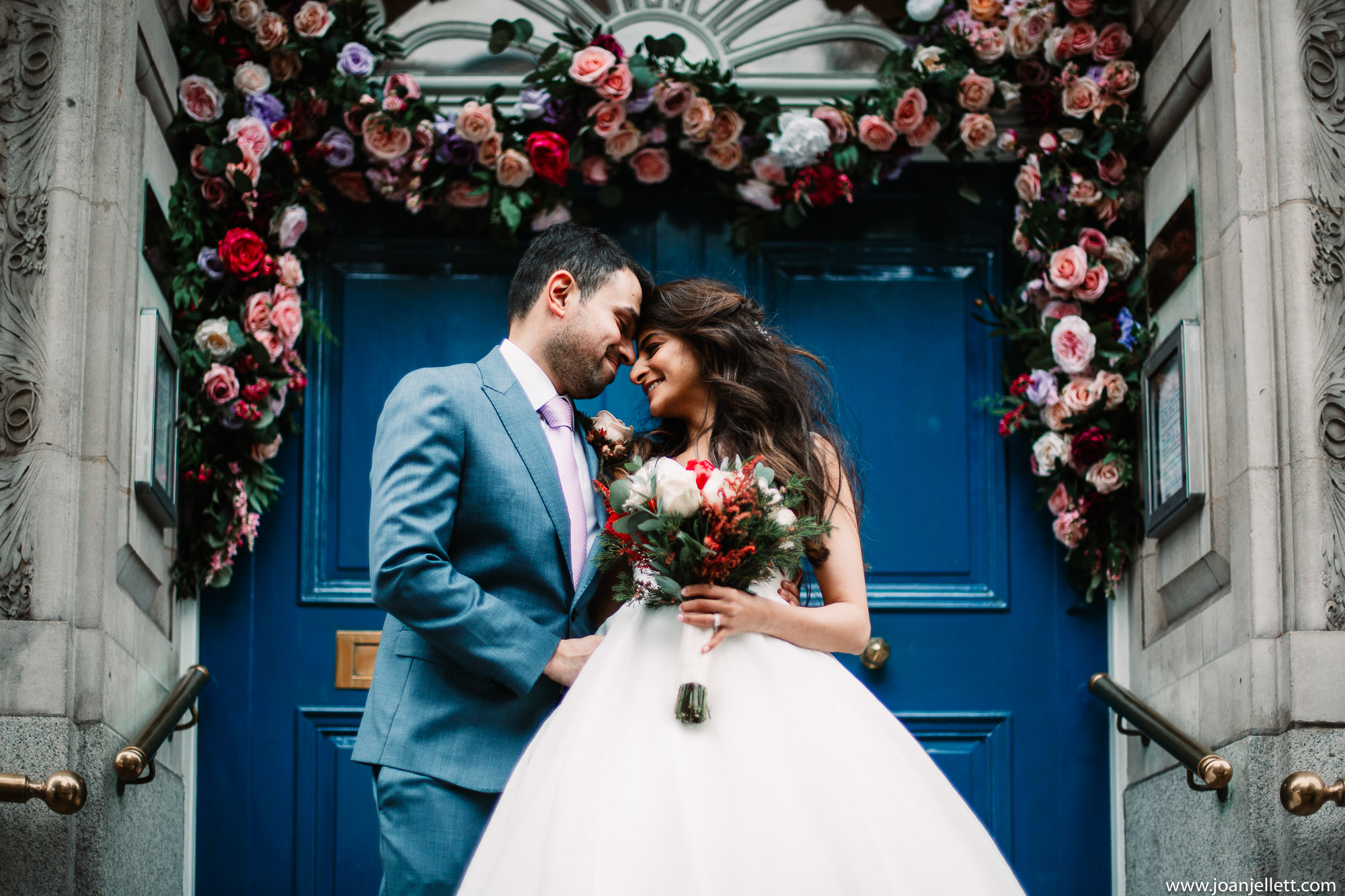 Bride and groom kissing on the steps of the Kensington and Chelsea Register Office office