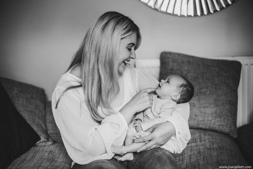 black and white shot of mum smiling at her newborn baby
